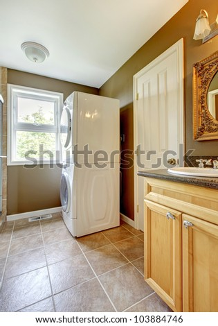 Laundry room with bathroom cabinet and sink and ceramic tiles. - stock photo