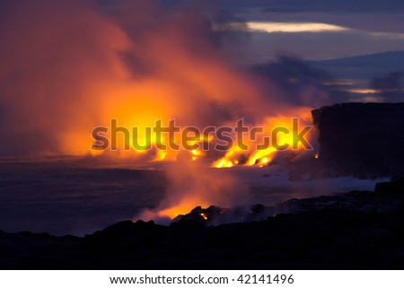 Lava erupting into Pacific Ocean at night on Big Island - stock photo