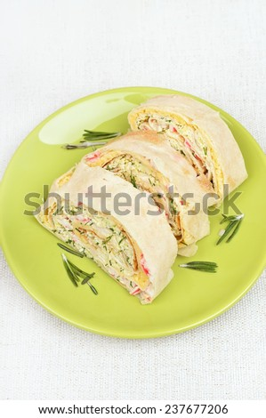 Lavash rolls with crab meat, cheese, eggs and herbs on green plate, top view - stock photo