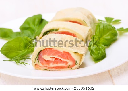 Lavash rolls with salmon, cheese and herbs on white plate - stock photo