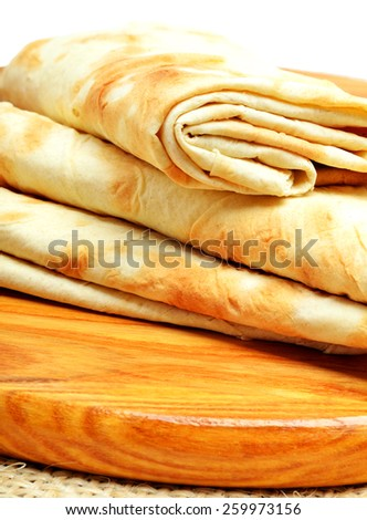 Lavash, tortilla wrap Bread on the cutting board isolated on white - stock photo