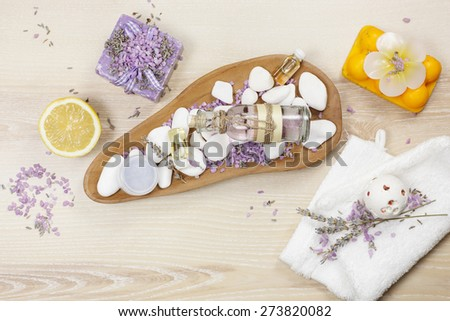 Lavender and lemon aromatherapy. Natural handmade lavender oil, soaps with bath salt, foaming bath bomb, lemon and lavender on wooden background - stock photo