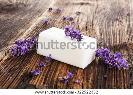 Lavender background. Fresh lavender blossom and lavender soap on brown aged wooden background, rustic country style. - stock photo