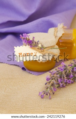 Lavender blossom honey. Lavender twigs in the background.Closeup - stock photo