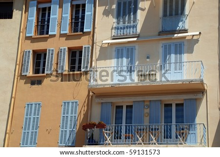 Lavender blue colored shutters on yellow stucco - stock photo