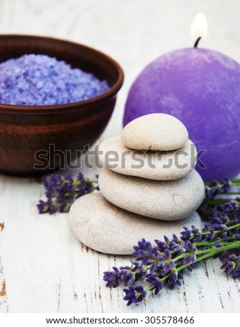 Lavender, candle and massage stones on a old wooden background - stock photo
