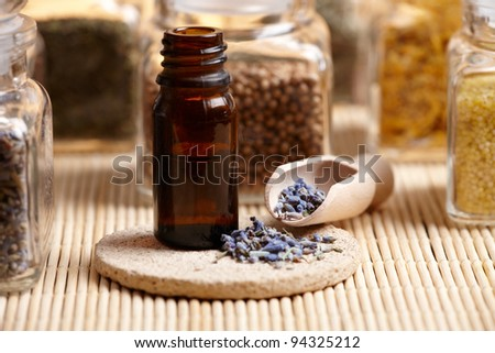 Lavender essential oil with dry lavendula flovers on wooden spoon with other herbs in background - stock photo