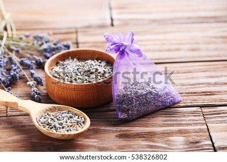 Lavender flowers in bowl and spoon on brown table