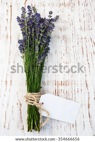 lavender flowers with tag on a old wooden background