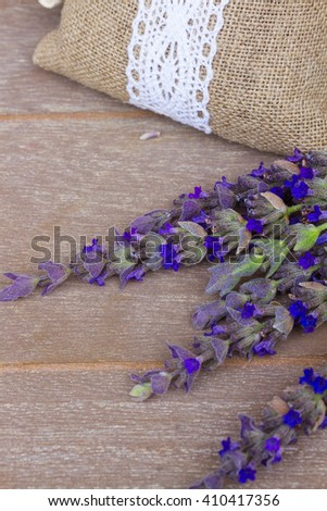 Lavender fresh flowers and dry ones in pouch on gray wooden table  - stock photo