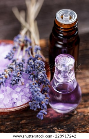 Lavender herb flower water in a glass bottle with flowers - stock photo