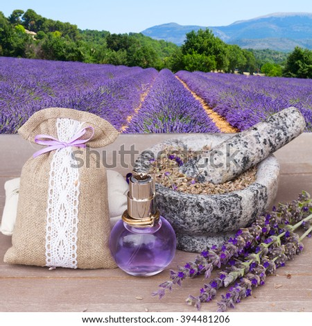 Lavender herbal water in a glass bottle with fresh and dry flowers in pouch on  table - stock photo