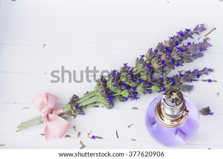Lavender herbal water in a glass bottle with fresh and dry flowers on white wooden table - stock photo