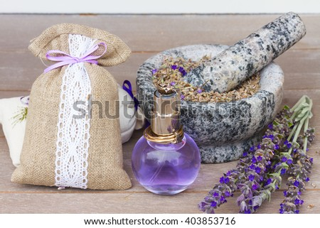 Lavender herbal water in a glass bottle with fresh and dry flowers on  wooden table - stock photo
