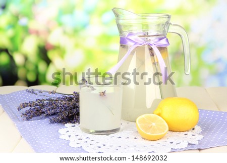 Lavender lemonade in glass jug and cocktail glasses, on bright background - stock photo