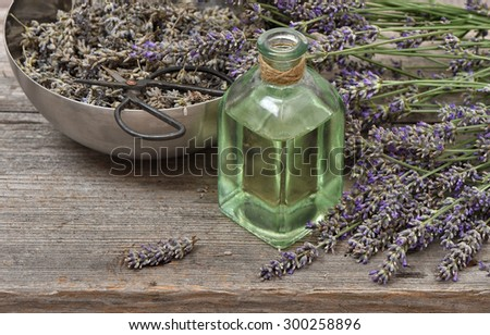 Lavender oil with fresh flowers on wooden background. Vintage style still life - stock photo