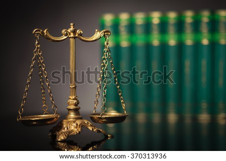 law and justice concept, antique golden scale in front of a row of law books in studio - stock photo