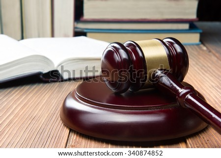 Law concept - Open law book with a wooden judges gavel on table in a courtroom or law enforcement office. - stock photo