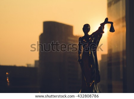 Law concept. Silhouette of Themis with building background. Statuette of justice. Statuette of the goddess of justice  - stock photo