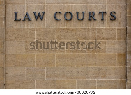 Law courts sign on an old stone wall with copy space. Law courts sign. - stock photo