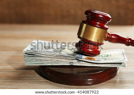 Law gavel with dollars on wooden table background, closeup - stock photo