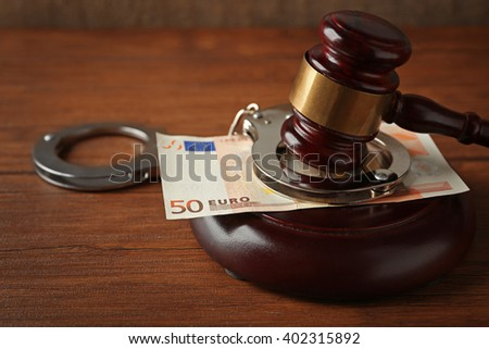 Law gavel with euro and handcuffs on wooden table background, closeup - stock photo