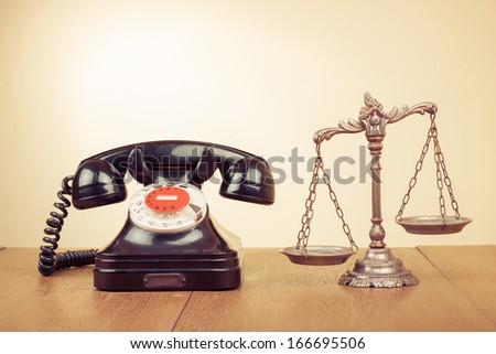 Law scales and retro telephone on table - stock photo