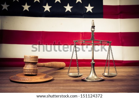 Law scales, judge gavel on table front of USA flag. Symbol of justice. Retro style photo - stock photo