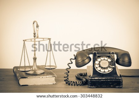 Law scales, old book and retro telephone on table. Vintage style sepia photo - stock photo