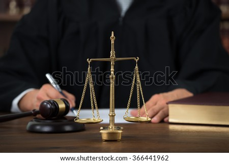 Law scales on table with judge writing in background at courtroom - stock photo