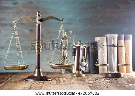 law theme, bronze and gold scales of justice, books, wooden mallet, statue of justice, books, on wooden table, studio shots, green wooden background, place for text and logo