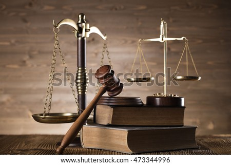 Law theme, bronze and gold scales of justice, books, wooden mallet, statue of justice, on wooden table, . Brown wooden background, studio shots