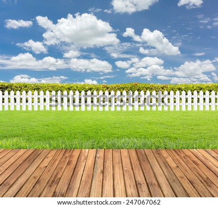 Lawn and wooden floor with hedge and White fence on blue sky background - stock photo