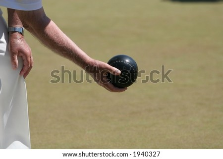 Lawn Bowl an forearm of an older gentleman on the green. - stock photo