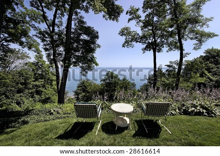 Lawn chairs and view of lake in luxury home - stock photo
