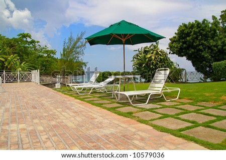 lawn-chairs by poolside - stock photo