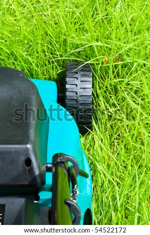 Lawn mover is going to be operated over long grass with backside view - stock photo