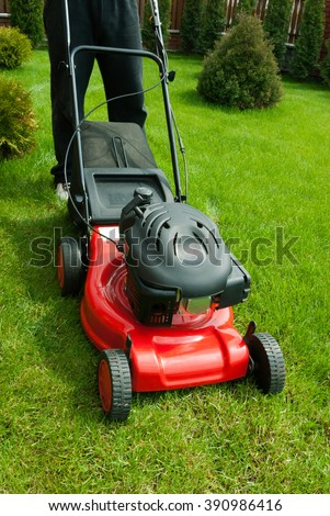 Lawn mower in the garden - stock photo