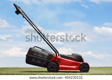 Lawn mower on a green grass and blue sky background - stock photo