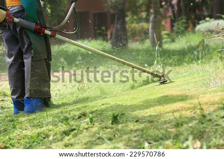 lawn mower worker cutting grass in green field. - stock photo