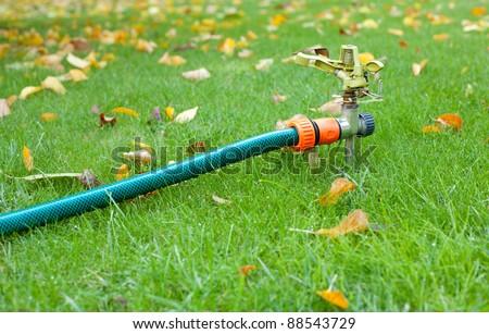 Lawn sprinkler over green grass in autumn garden - stock photo