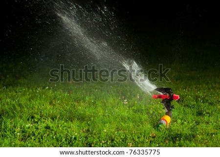 lawn sprinkler spraying water over green grass at night - stock photo