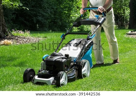 Lawnmower is being used by gardener for mowing grass - stock photo