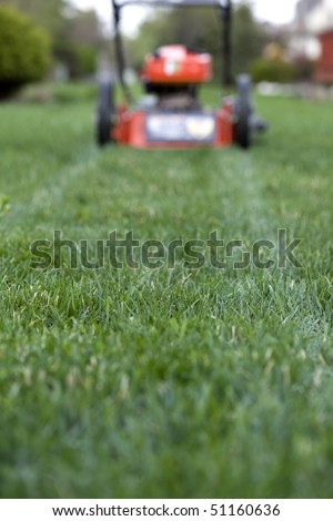 lawnmower on the far side of a lawn - stock photo