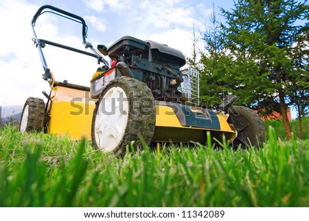 Lawnmower standing on green grass - stock photo