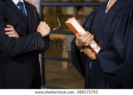 Lawyer holding a law book in office - stock photo