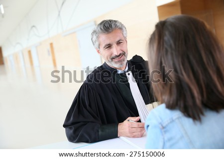 Lawyer meeting client in courthouse before trial - stock photo