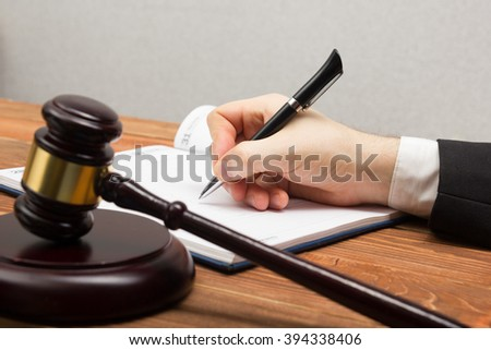 Lawyew working. Notary public signing document at his workplace. - stock photo