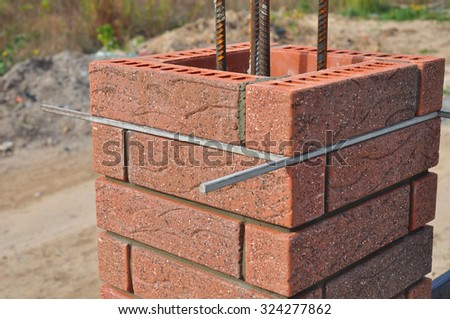 Lay bricks and blocks correctly. Closeup. Whether you are laying brick to build a mailbox enclosure, or building a brick house, the process is the same. - stock photo