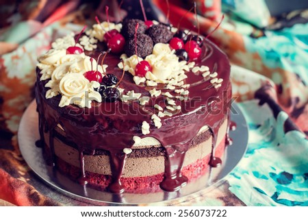 Layer cake decorated with chocolate glaze, cream flowers and cherries on colorful fabric background. vintage stylized photo - stock photo